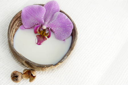 swimming candles: Orchid flower in milk in a coconut on a light background, preparation for a spa treatment, relaxing atmosphere, postcard