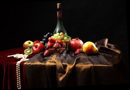 Pearl beads lie on the edge of the table, classic Dutch still life with dusty bottle of wine and fruits on a dark background, horizontal. Stock Photo