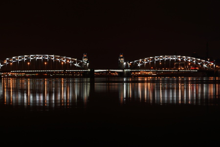 Drawbridge in St. Petersburg, illuminated by lights and reflected in the river Neva.