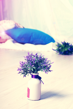 A vase with flowers stands on the floor in the room, special toning and highlighting. Stock Photo