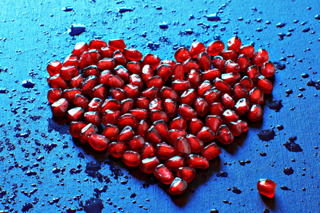 Heart of ripe red pomegranate seeds on a blue background, splashes, blots and drops of water, healthy food. Stock Photo