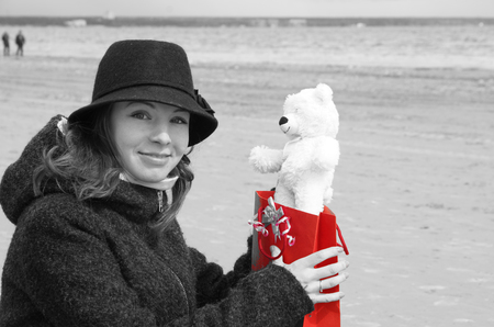 dreaminess: A young beautiful girl in a hat sits on the shore of the bay and is happy to receive a teddy bear as a present, a black and white picture with a red color Stock Photo