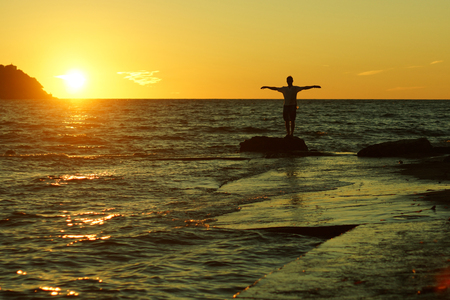 Silhouette of a man standing on a rock with raised perpendicular hands on a sunset background on the seashore