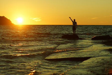Silhouette of a man standing on a rock with his hand raised upwards with his fingers spread out against the sunset on the beach.