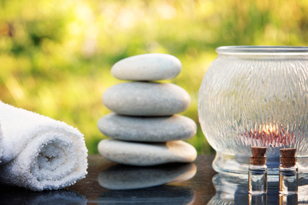 A spa treatment set, massage stones, a towel and massage oil are placed on a polished granite table in the garden Stock Photo