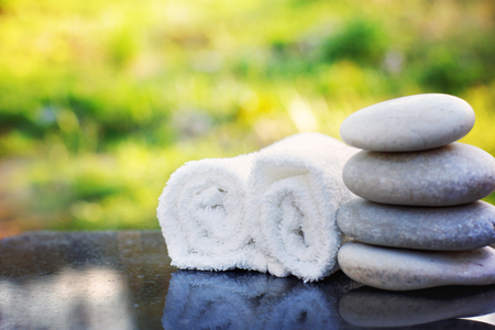 A spa treatment set, massage stones and a white terry towel on a polished granite table in the garden