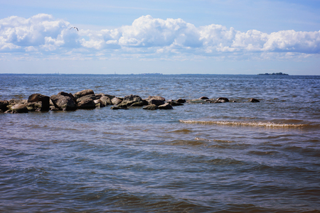 A stone ridge peeps out of the water in the sea bay, large waves of tide, cumulus clouds on the horizon. Stock Photo
