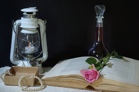 untruth: Horizontal still life on a black background with a book, an old lantern and a bottle of wine, a pink rose lies between the pages, next to a set of pearl jewelry in a cardboard box.