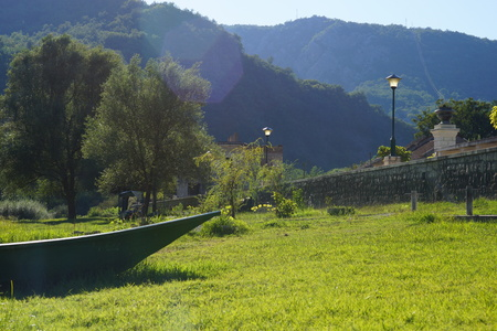 The nose of the boat on the bank of the river on the grass, next to the embankment with lanterns, on the horizon high mountains, overgrown with forest. 版權商用圖片