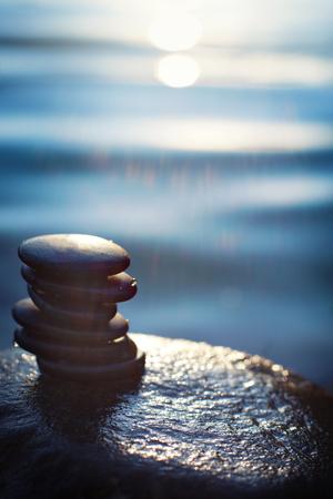 スパのプロシージャのための石は青い水、太陽の光に照らされたの背景に、濡れた岩を山の上うそをつきます。 写真素材 - 82058895