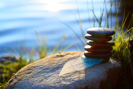 Stones for spa procedures lie on a pile on a boulder near the lake, illuminated by the suns rays. Stock Photo