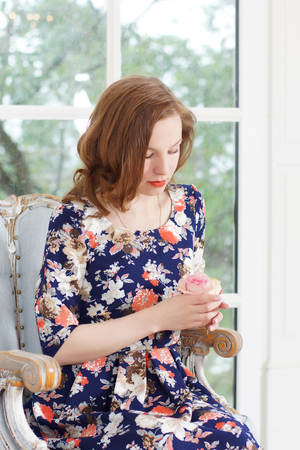 A beautiful young girl in a bright colorful dress sits in an armchair by the window and looks thoughtfully at the rose in her hands