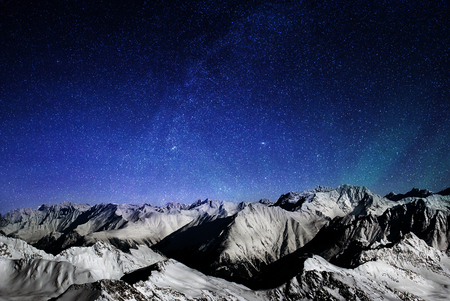 Mountains of the Alps at night, snowy peaks of a mountain range under a large starry sky