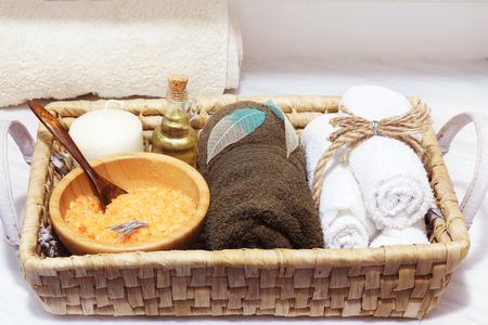 Wicker basket with spa treatment set, sea salt, aromatic oil, stones, candle and soft towels decorated with skeletonized leaves.