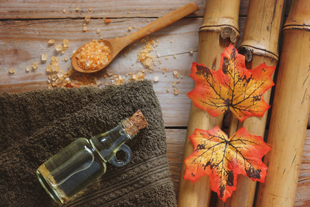 Spa background with bamboo, bath salt, massage oil, autumn leaves and towel. Banco de Imagens