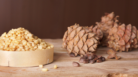Cedar cones and pine nuts are on a wooden table