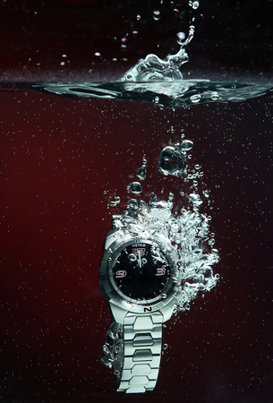 The wristwatch is immersed in water with a splash and bubbles.