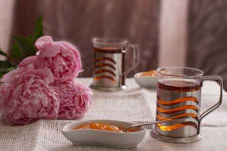 A cup of hot tea next to a saucer with dessert and three peony flowers, breakfast for two.