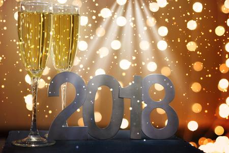 Stralen markeren 2018 op een nieuwjaarskaart met champagne en guirlandes.