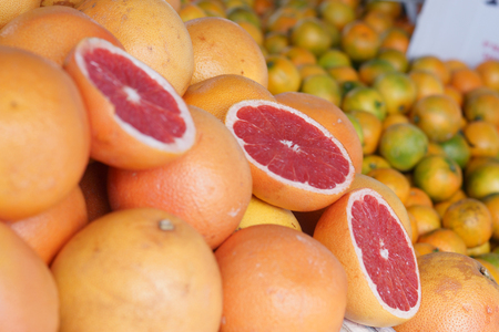 Grapefruits lie on the counter in the market, cut halves attract buyers.