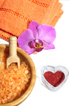 Spa set from orange bath salt, towel with orchid flower and red heart on Valentines Day.