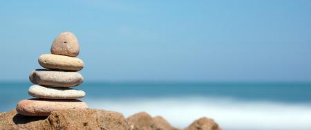 Piramide van stenen aan de oever van de blauwe zee, harmonie, panoramisch Stockfoto - 90515752