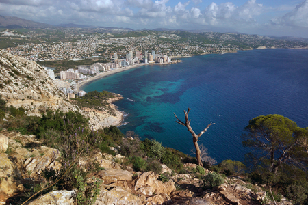 View from the mountain Ifach on a steep stony slope, the blue sea and coastal town of Kalp on the Mediterranean coast in Spain, the Costa Blanca region.