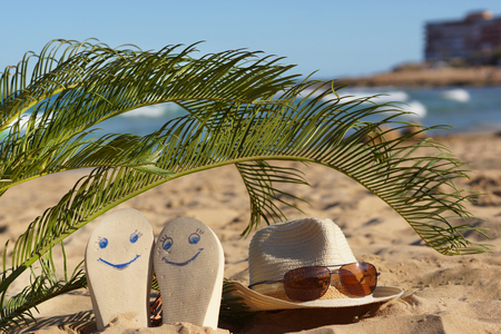 Beach slippers with painted happy faces and a hat with sunglasses under palm leaves on the sand near the sea.