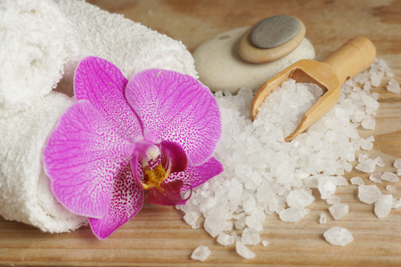 Spa set with white towels, sea salt, wooden spatula and bright orchid flower. Stock Photo