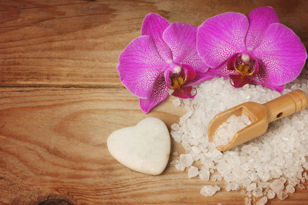 Spa set with white sea salt, wooden spatula and bright orchid flower, heart-shaped stone.