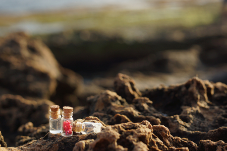 Glass jars filled with stoppers, filled for spa treatments, on rocks near the sea in the morning. Stock Photo
