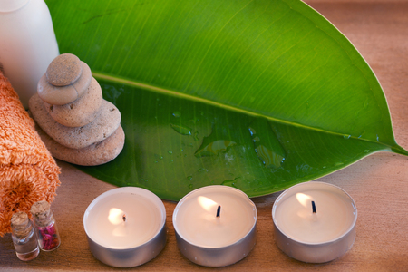 Spa set with an orange towel and candles on a green leaf. Stock Photo