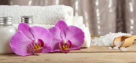Set for spa treatments with lotions for skin, orchid flowers, bath salt and white towels.