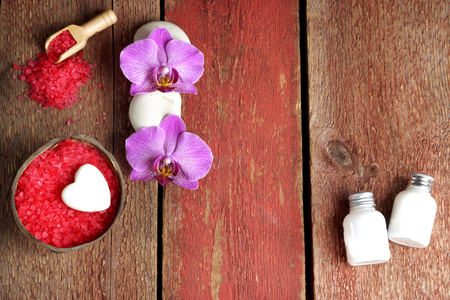 Spa set with red bath salt, orchid and towel flowers, lotion and soap on a wooden background.