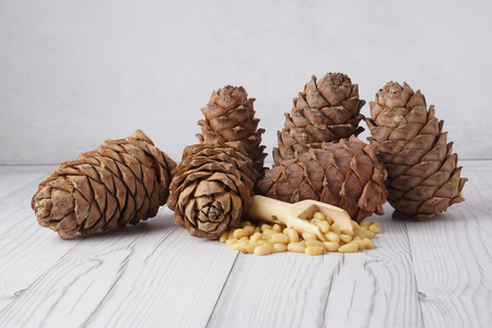 Many cedar cones and nuts in a wooden spatula on a light background