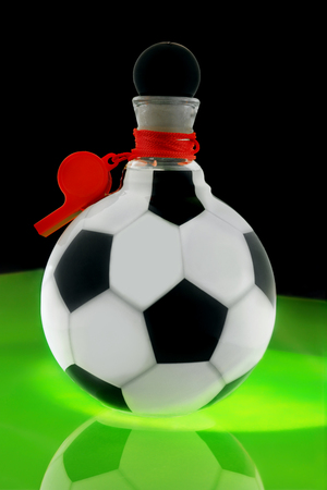 Bottle in the form of a soccer ball with a red referee whistle on a green table simulating a football field. Stock Photo