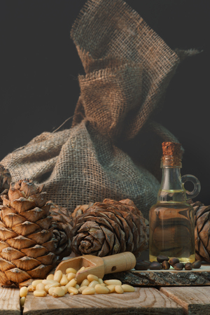 Cedar cones and nuts next to a bag of matting and a bottle of oil