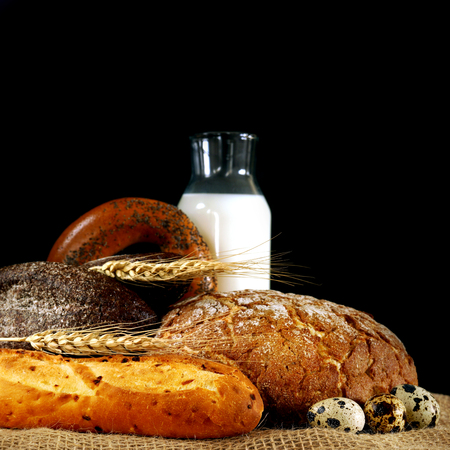 Wheat spikes and bread on the table with a bottle of milk Standard-Bild