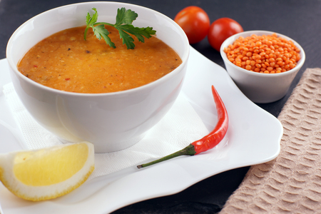 Lentil soup in a plate, next to vegetables and a slice of lemon. Stock Photo