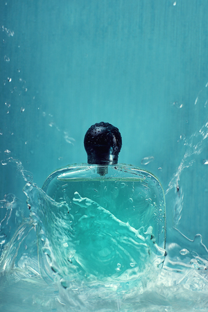 A bottle with perfume on a blue background with splashes of water that fly in all directions. Stock Photo