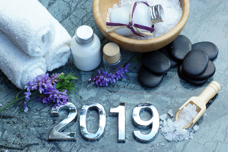 Set for spa treatments in 2019 on marble stone with candles, figures, bath salt and towels, horizontal. Stock Photo