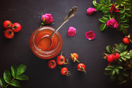 Spoon in a jar of rosehip jam and its berries with leaves nearby, top view. Banco de Imagens