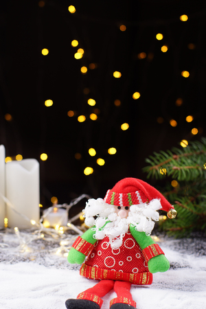 Santa Claus toy on the background of luminous garlands, white candles and Christmas fir Stock Photo