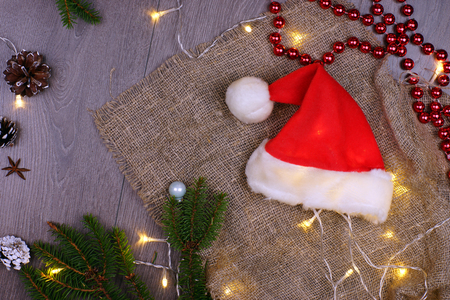 Traditional Santa Claus hat on a wooden background next to a luminous garland, fir branches, pine cones and red beads. New year concept. Greeting christmas card. Flat lay. Stock fotó