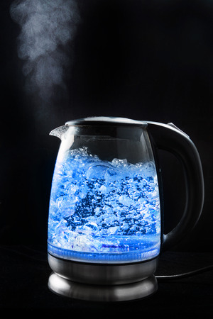 Boiling glass kettle with blue light on a black background, steam comes from the spout 스톡 콘텐츠