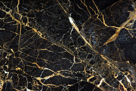 The surface of the slab of dark expensive marble with yellow and white veins is called New Portoro.