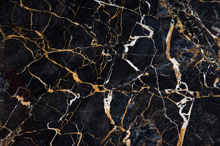 A beautiful pattern on the surface of a slab of black marble with yellow and white veins called New Portoro.