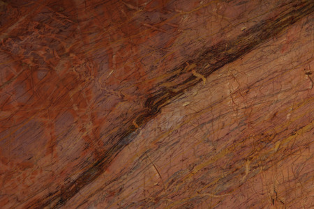 Natural stone of red color with yellow and claret veins. Imagens
