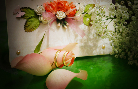 Gold wedding rings are put on the rosebud against the background of the greeting card and the bouquet.