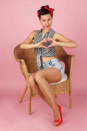 Beautiful brunette woman folded her hands in the shape of a heart, pin-up style on a pink background